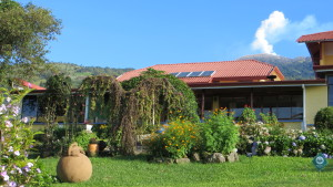 Front garden of the lodge with smoking Turrialba volcano