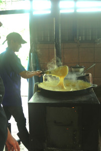 Boiling and stirring the corn pudding on a wood stove