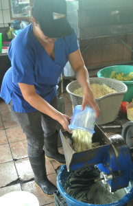 Grinding cooked corn into a paste with whey water