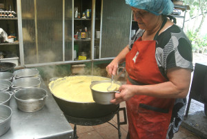 The corn pudding is scooped into the molds